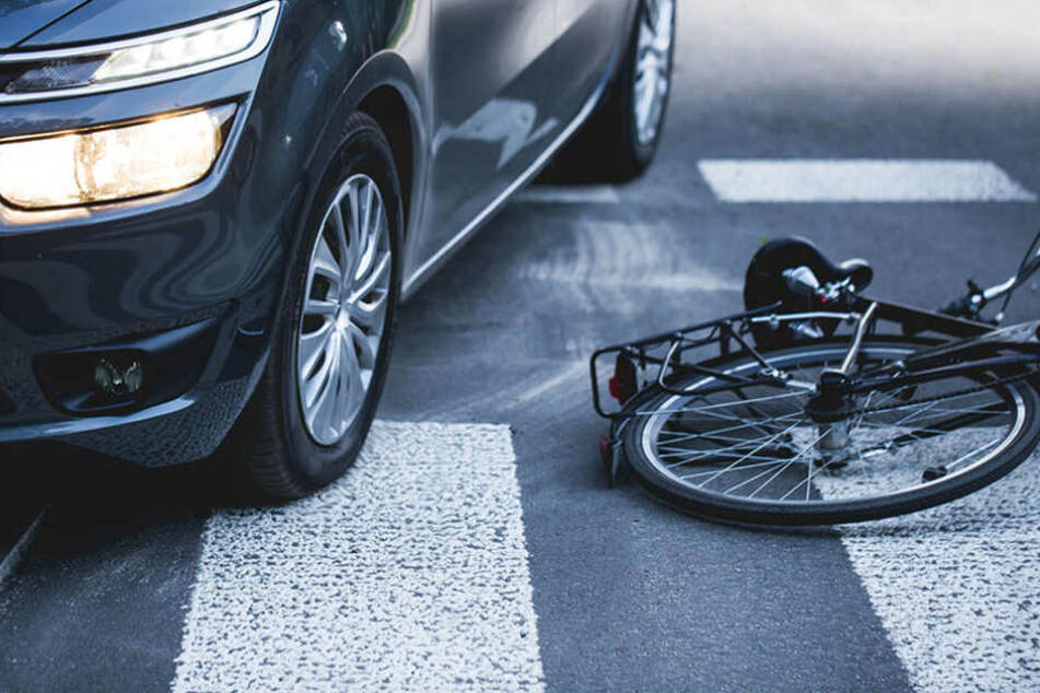Das Radfahrer wollte Ein Fahrrad liegt nach einer Kollision mit einem Auto auf der Straße. (Symbolbild)