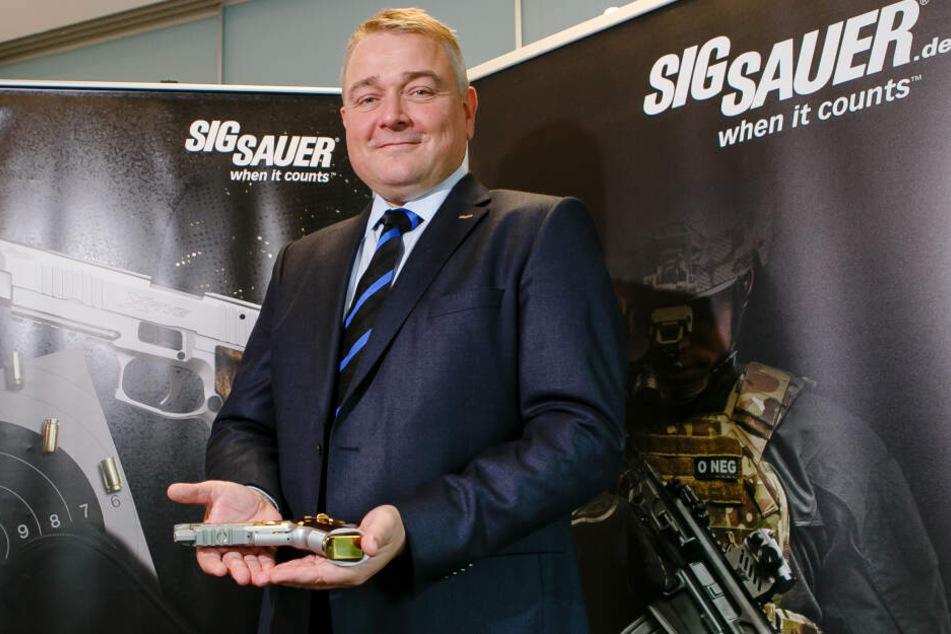 Der deutsche Sig Sauer-Geschäftsführer Tim Castagne hält eine P226 X-Five Violine-Sportpistole in den Händen.