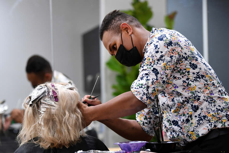 Ein Friseur arbeitet mit Schutzmaske.