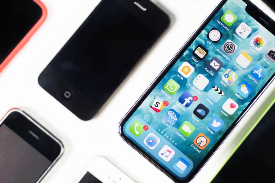 Ein iPhone X liegt neben iPhones anderer Generationen auf einem Tisch (Archivbild).