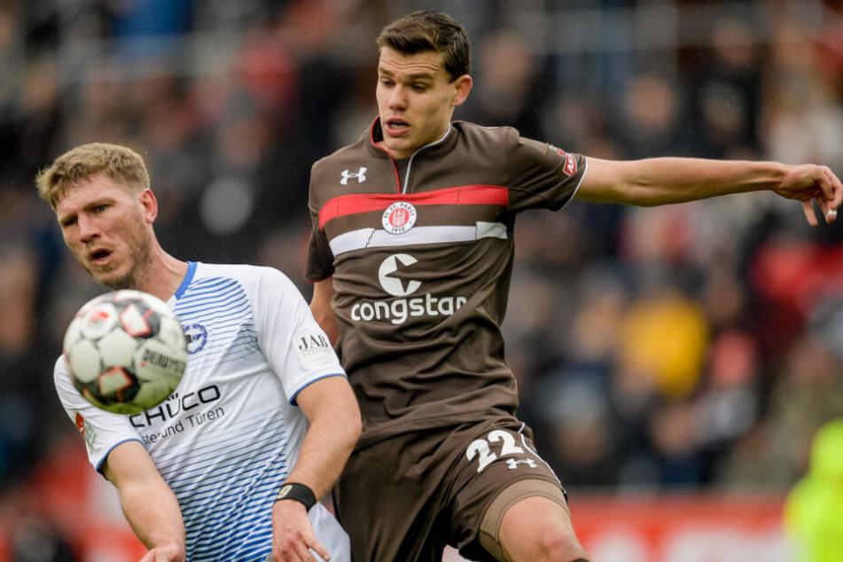 St. Paulis Abwehrspieler Justin Hoogma kommt gegen Bielefelds Angreifer Fabian Klos nicht an den Ball.
