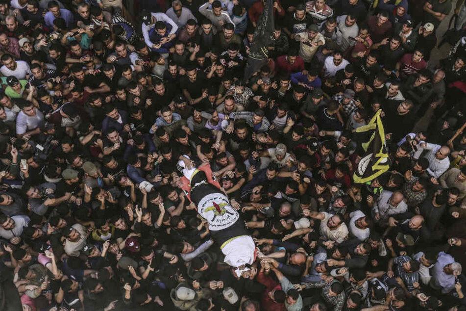 Trauernde tragen den eingewickelten Körper von Baha Abu Al Ata bei dessen Beerdigung.