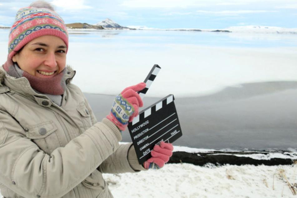 See Mývatn, Island: Bloggerin Andrea David hält eine Filmklappe in die Höhe. Die Hamburgerin bereist Filmkulissen in der ganzen Welt und berichtet auf ihrem Blog und ihrem Instagram-Feed darüber.