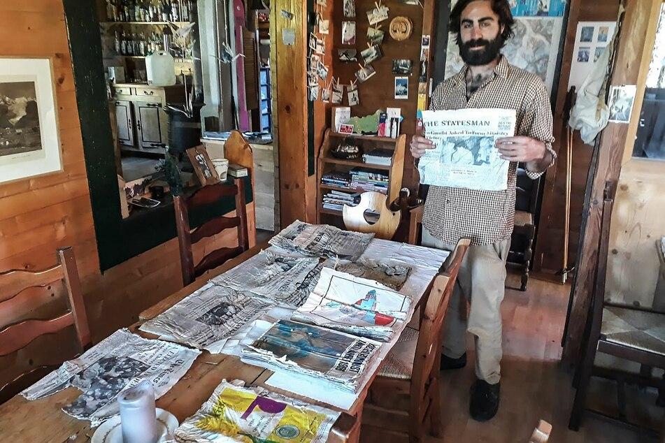 """Thimotee Mottin, Leiter des Café-Restaurants Cabane du Cerro, hält eine Ausgabe einer Zeitung in der Hand, die sich wahrscheinlich an Bord der Boeing 707 """"Kangchenjunga"""" der Air India befand."""