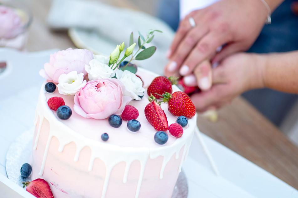Ein Brautpaar schneidet eine Torte bei der Hochzeitsfeier an.