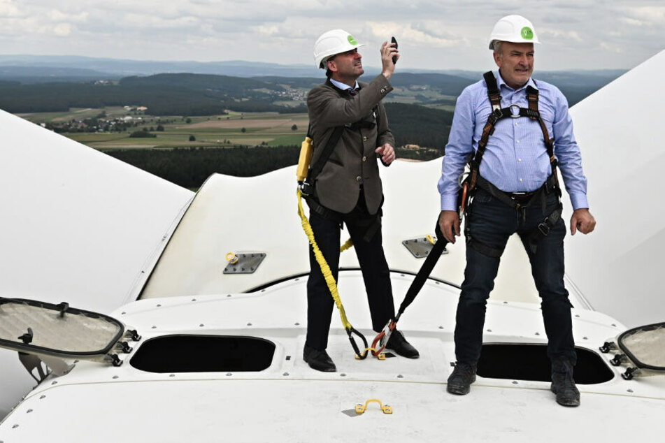 Der bayerische Wirtschaftsminister Hubert Aiwanger (l.) und der Geschäftsführer der Bürgerwindenergie Gebenbach GmbH & Co. KG, Erich Wust, stehen auf dem Gondeldach des Windrads des Bürgerenergieparks Gebenbach.