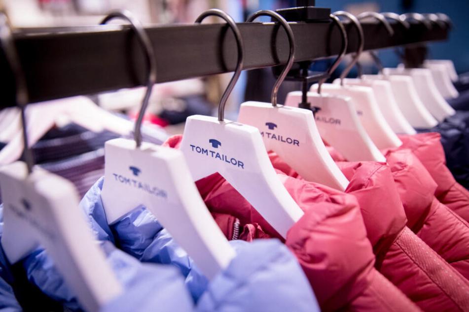 Jacken der Marke Tom Tailor hängen auf Kleiderbügeln in einem Geschäft.
