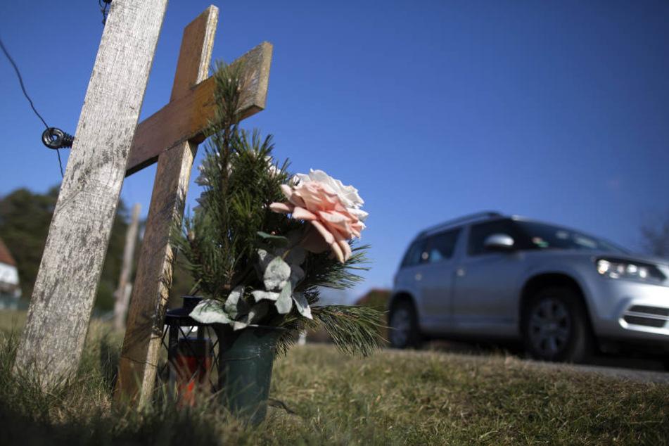 Ein Auto fährt an einem Kreuz zur Erinnerung an einen Verkehrstoten auf einer Landstraße vorbei.
