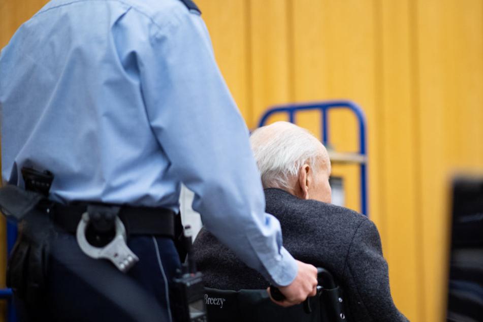 In einem Rollstuhl wird der ehemalige SS-Wachmann in den Gerichtssaal geschoben.