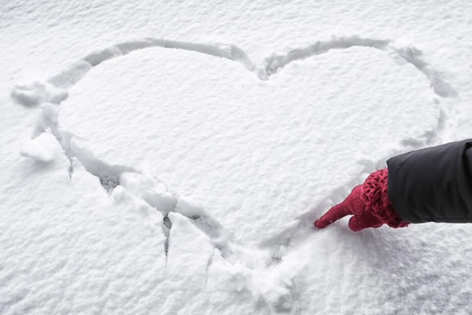 Eine Frau malt ein Herz in den Schnee: Auch beheizbare Handschuhe sind mittlerweile voll im Trend.
