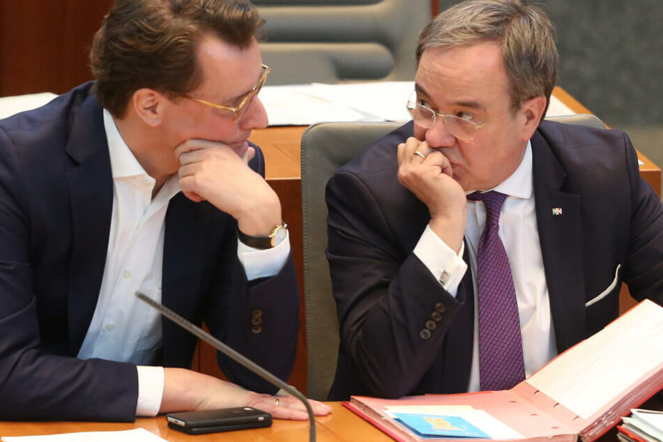 Der nordrhein-westfälische Verkehrsminister Hendrik Wüst (CDU, l) spricht auf der Ministerbank mit Ministerpräsident Armin Laschet (CDU).