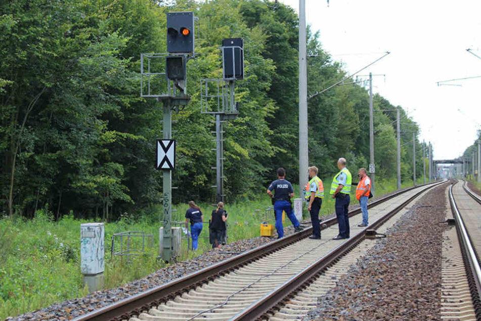 Mitarbeiter der Bahn und der Polizei untersuchen am Gleisbett eine Signalanlage an der Bahnstrecke in der Nähe von Finkenkrug bei Berlin.