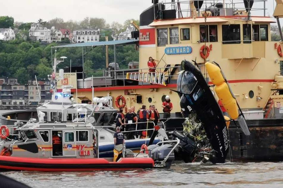 Rettungskräfte ziehen den Helikopter aus dem Wasser.