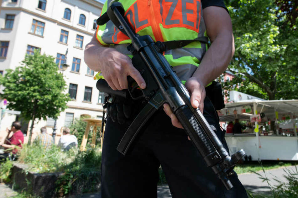 Ein Polizist steht mit der Waffe im Anschlag an der Wegstrecke beim Umzug beim Karneval derKulturen.