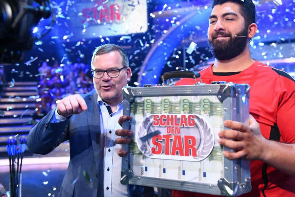 Faisal Kawusi bekommt von Moderator Elton das Preisgeld überreicht.