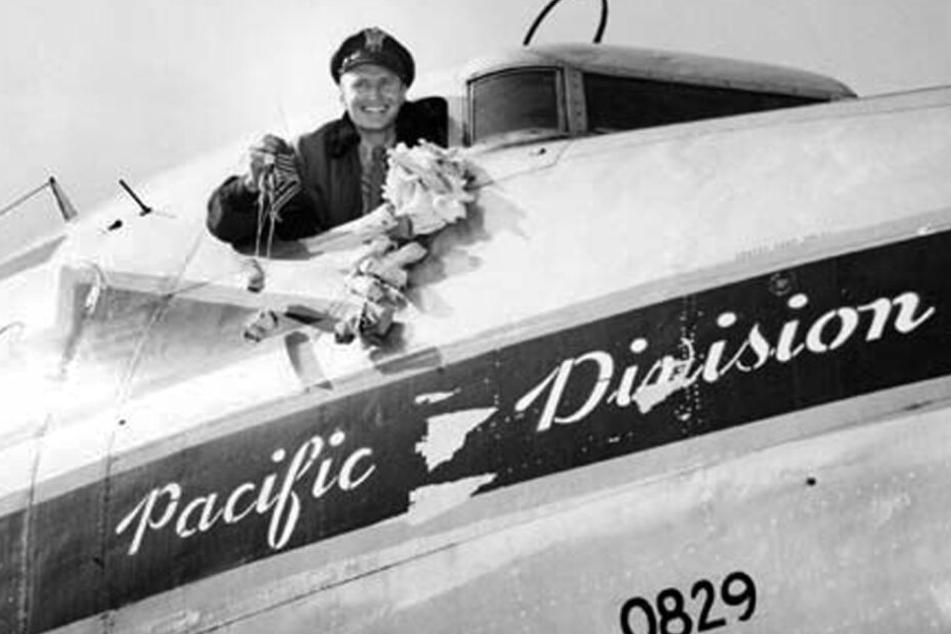 """Das Foto zeigt einen amerikanischen Piloten, der 1948 in Frankfurt einen """"Candy drop"""" andeutet."""
