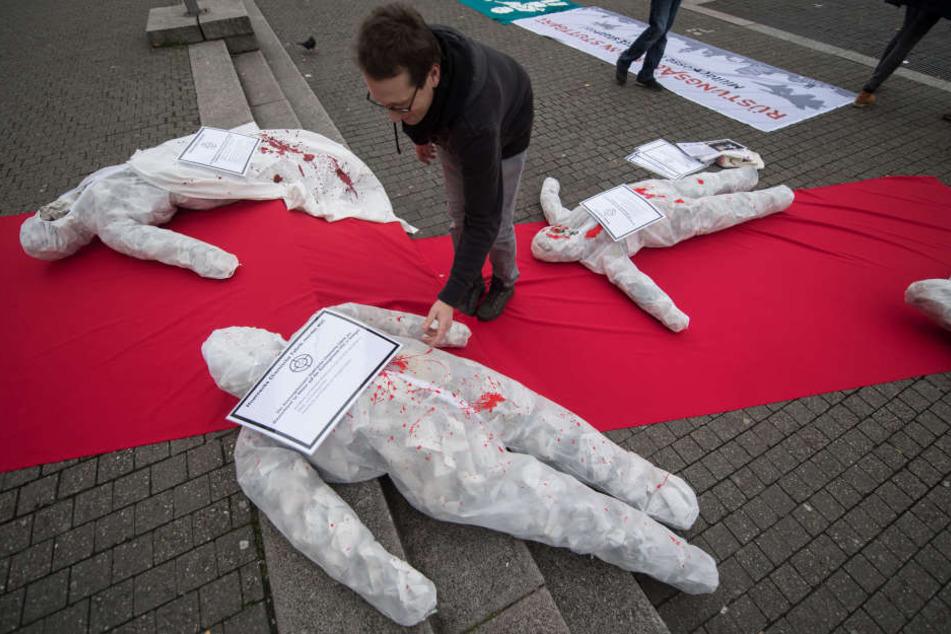 Ein Rüstungsgegner legt vor dem Rathaus bei einer Kundgebung von Rüstungsgegnern gegen die Militärmesse ITEC ein Plakat auf ein symbolisches Kriegsopfer.