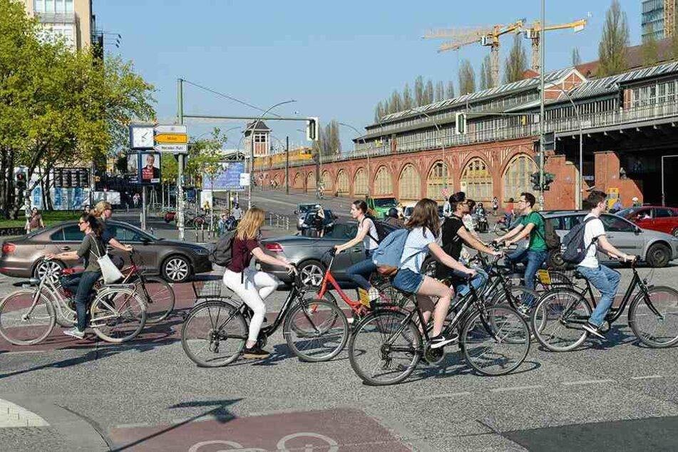 Fahrradfahrer und Autos befahren in Berlin an der Oberbaumbrücke die Kreuzung Mühlenstraße und Warschauer Straße.