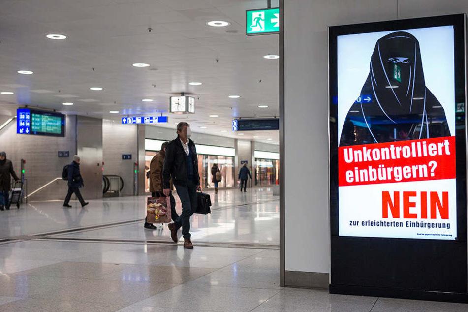 Ein Plakat mit einer vollverschleierten Frau hängt im Züricher Hauptbahnhof.