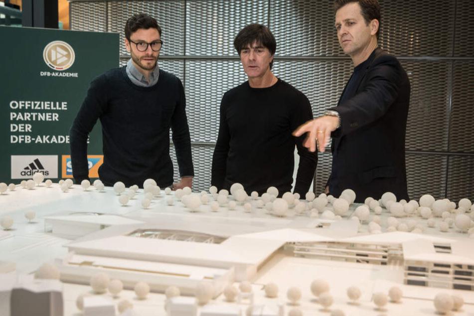 Jonas Hector (Li.), Bundestrainer Joachim Löw (Mi.) und Teammanger Oliver Bierhoff vor einem Modell der zukünftigen DFB-Akademie.