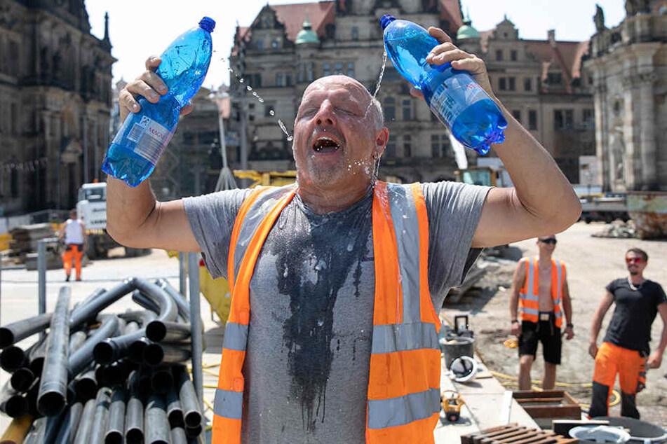 Diese Hitze! Hentschke Bau-Vorarbeiter Uwe Juchler (52) gönnt sich am Schloßplatz eine Wasserdusche.
