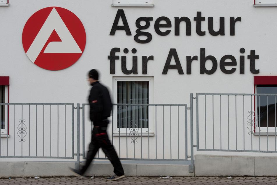 Ein Mann geht an dem Logo der Agentur für Arbeit vorbei. (Symbolbild)
