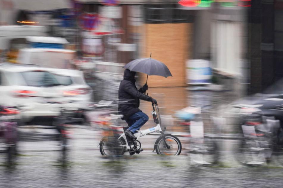 Ein Radler schützt sich während der Fahrt durch Frankfurt mit einem Schirm vor der Nässe.