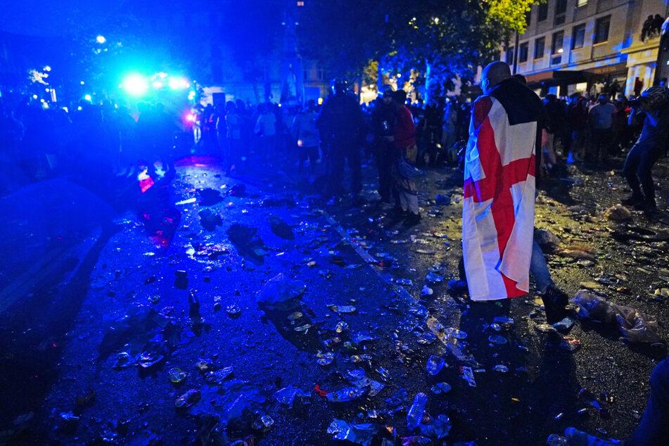 Ein englischer Fan, der in eine Flagge gehüllt ist, geht durch Müll und zerbrochenes Glas auf dem Trafalgar Square.
