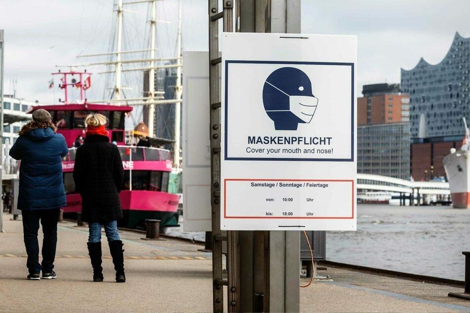 """Ein Hinweisschild mit der Aufschrift """"Maskenpflicht"""" hängt an den Landungsbrücken in Hamburg."""