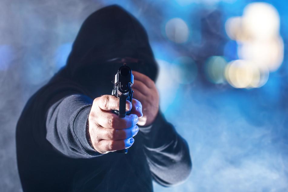 Einer der maskierten Räuber soll die Tankstellen-Mitarbeiterin mit einer Pistole bedroht haben. (Symbolbild)