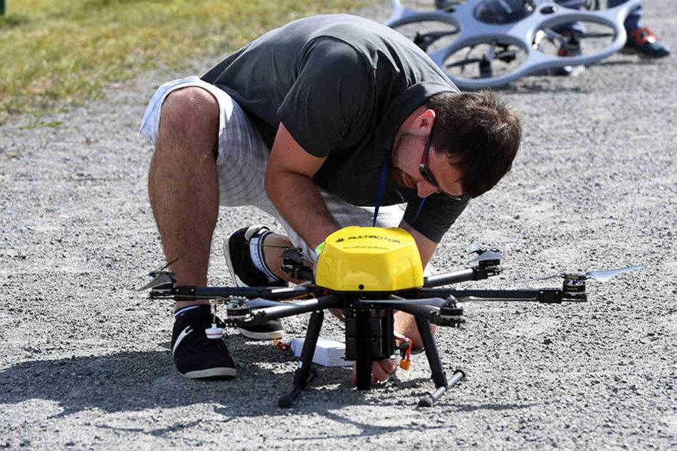in Mann justiert bei dem Dronemasters Dronathon in Berlin eine Multicopter-Drohne.