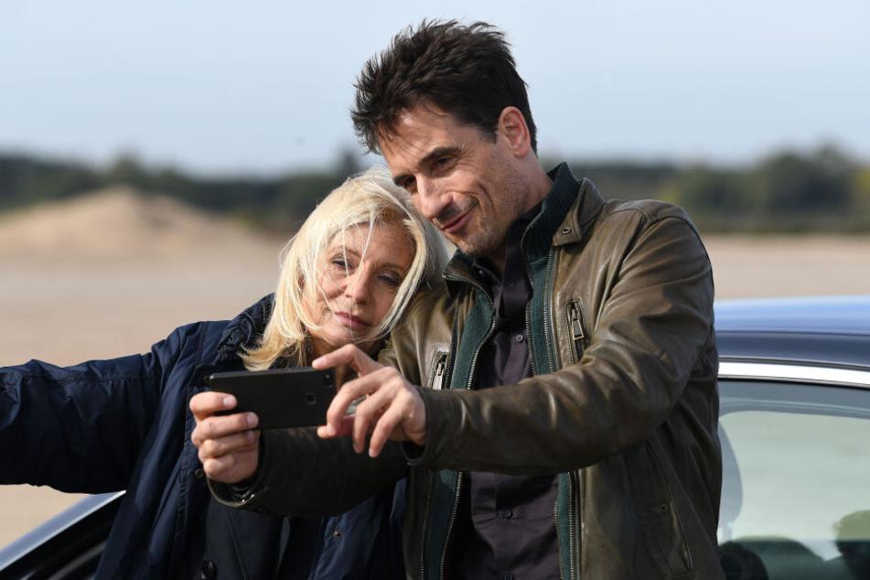 Schauspieler Oliver Mommsen macht mit Schauspielerin Sabine Postel am Rande der Dreharbeiten ein Selfie.
