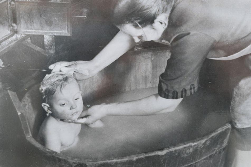 Waschtag in der Badeanstalt. Hals und Haar - alles rubbelt die Mama sauber.