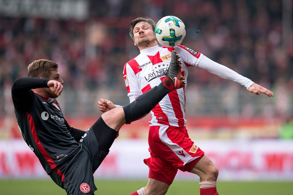Düsseldorfs Rouwen Hennigs (l) streckt den Fuß zum Ball gegen Unions Michael Parensen.