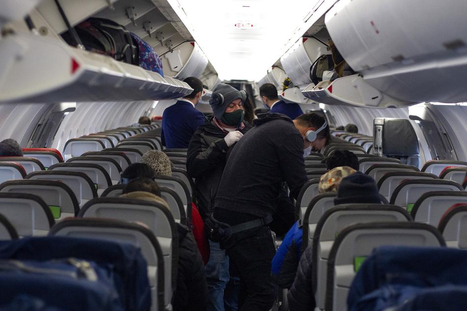 Passagiere mit Mundschutz steigen in ein Flugzeug.