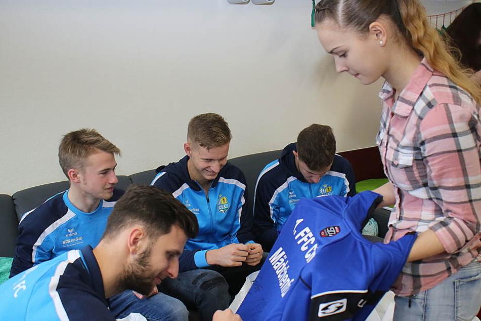 CFC-Spieler beim Signieren der Trikots.