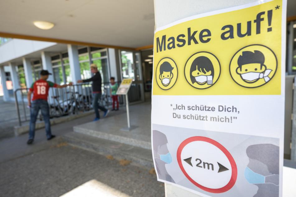 Ein Plakat weist auf die Maskenpflicht in der Berufsbildenden Schule 1 Gewerbe und Technik (BBS1) in Mainz hin.