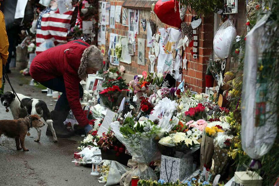 Menschen legen am 25.12.2017 in Goring-on-Thames, Oxfordshire, Blumen, Kerzen, Fotos und andere Gegenstände vor dem Haus des britischen Sängers George Michael nieder, um an dessen ersten Todestag an ihn zu erinnern.