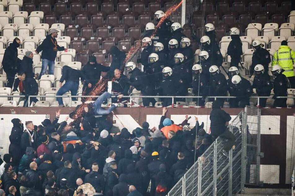 Polizeikräfte drängen randalierende Fans von Dynamo Dresden zurück in den Gästeblock.