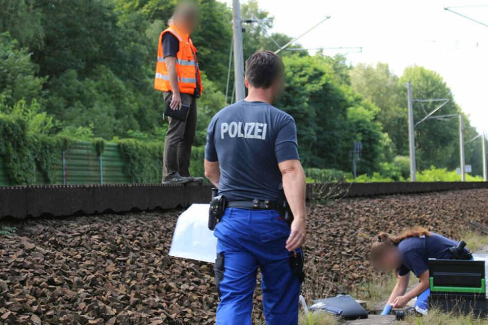 Mitarbeiter der Bahn und der Kriminalpolizei untersuchen am Samstag am Gleisbett einen Kabelschacht an der Bahnstrecke in der Nähe von Groß Behnitz bei Berlin.
