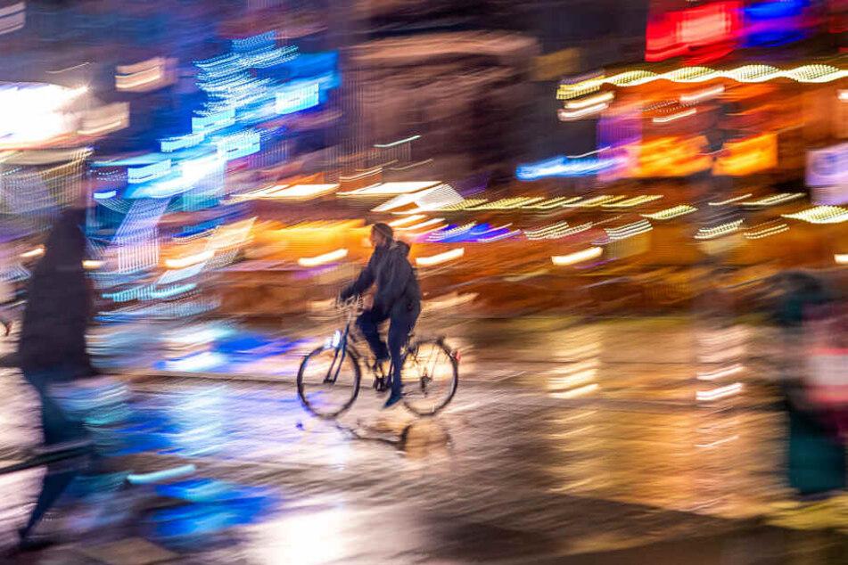 Ein Radler fährt bei Regenwetter durch die Dresdner Altstadt.