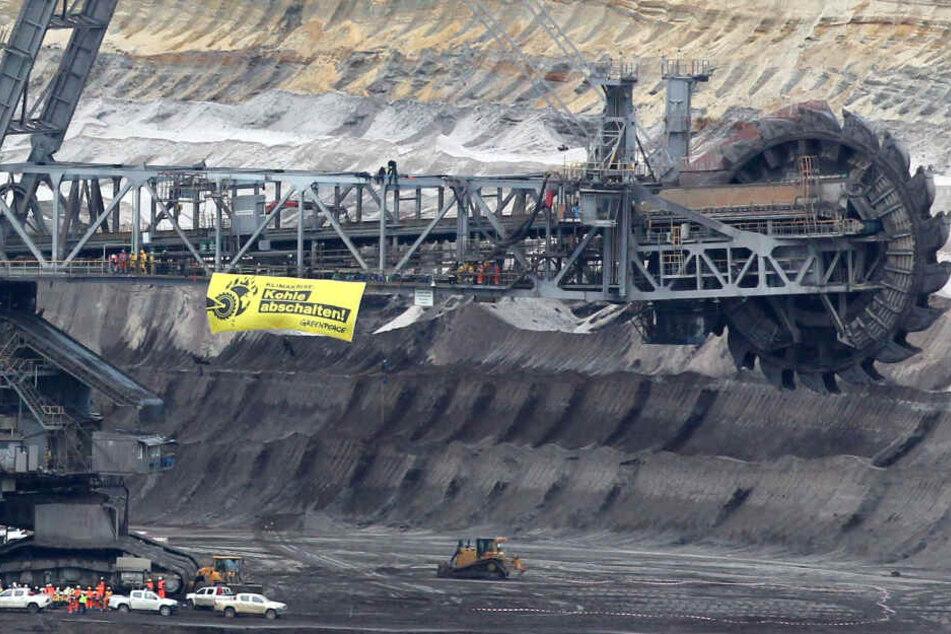 """An einem Braunkohle-Bagger hängt ein Plakat mit der Aufschrift """"Kohle abschalten ! Greenpeace""""."""