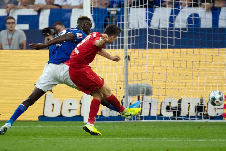 Schalkes Salif Sane (l) kann Bayerns Robert Lewandowski nicht davon abhalten, das 3:0 zu erzielen.