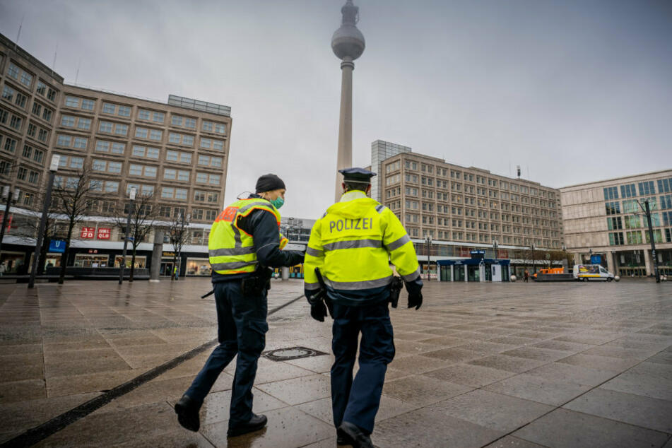 Polizisten gehen über den ansonsten weitgehend leeren Alexanderplatz in der Hauptstadt.