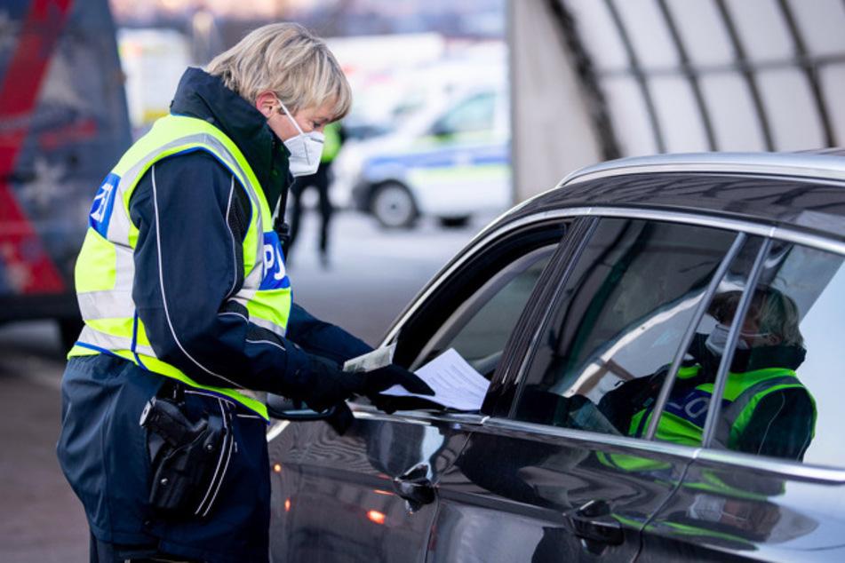 Eine Bundespolizistin kontrolliert die Dokumente eines aus Österreich kommenden Reisenden an einer Kontrollstelle an der Autobahn A93 bei Kiefersfelden in Richtung Deutschland.