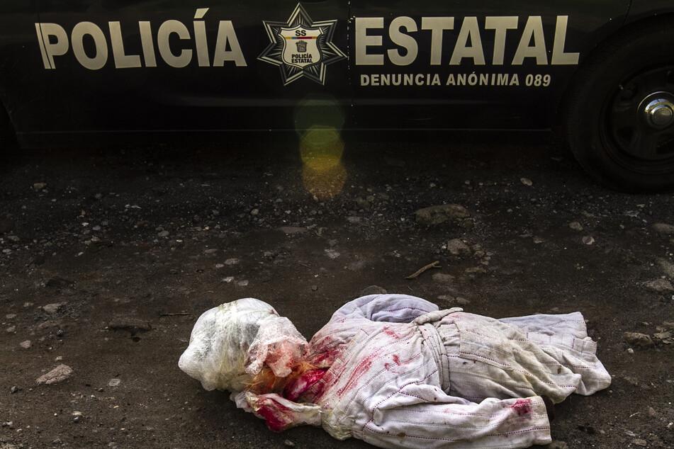 Eine mit rot gefärbte Puppe liegt auf der Straße. Die Puppe trug eine Drohnachricht, die an Drogenverkäufer adressiert war (Symbolbild).