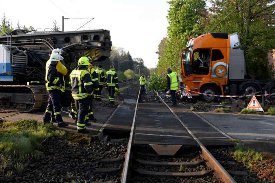 Die Einsatzkräfte stehen an der Unfallstelle, am Lkw sind die Spuren des Zusammenpralls deutlich zu sehen.