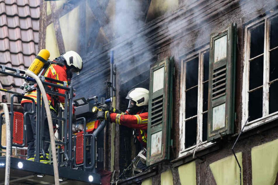 Ein Feuerwehrmann kommt aus einem Fenster in dem brennenden Haus und wird von seinem Kollegen an der Drehleiter gesichert.