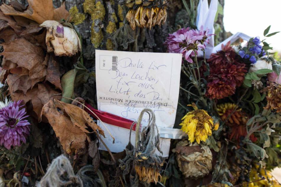 Blumen und Trauerschmuck hängen an einem Baum an der Dreisam. Hier soll der Täter sein Opfer getötet haben.