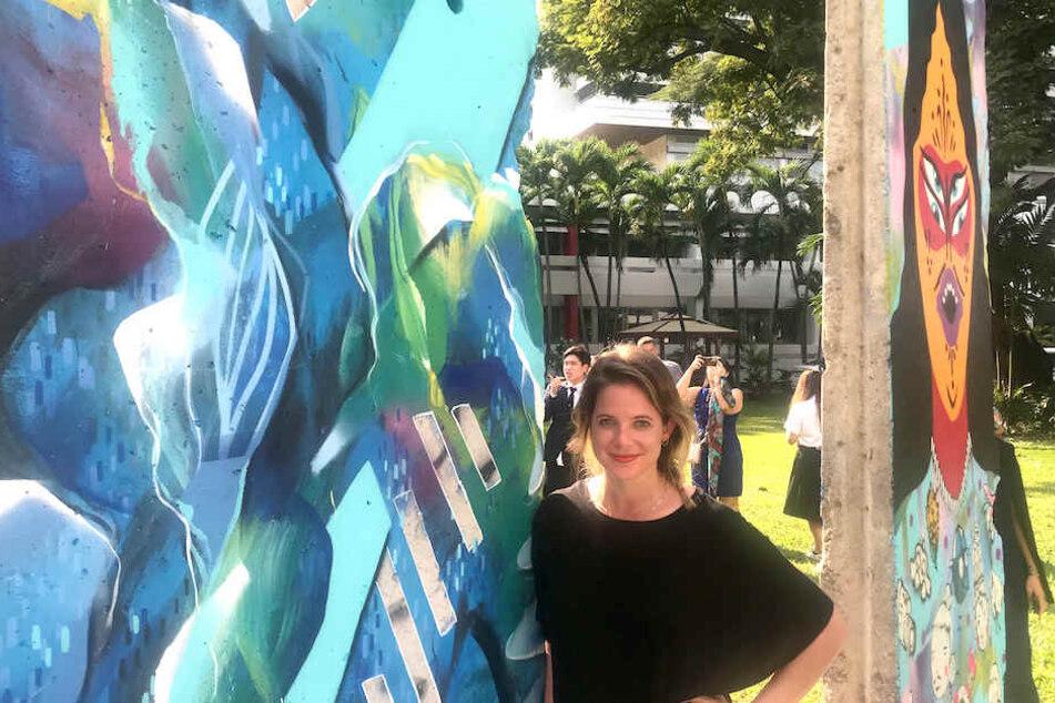 Die Berliner Künstlerin Julia Benz (33) mit den von ihr mitbemalten Teilen der Mauer.